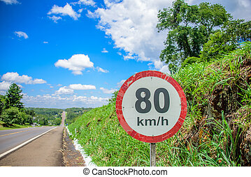Sign of 80 kilometres per hour limit on the background of small hill covered with grass, long road going to horizon and blue sky