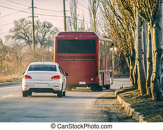 White car and red bus on the road