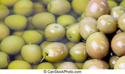 Pouring olive oil on green olives