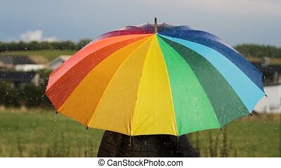 A person with rainbow colored umbrella in the rain hd video