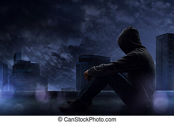 Man sitting on the rooftop in a rainy night