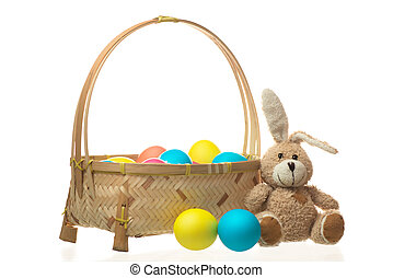 teddy rabbit near a basket of colorful Easter eggs isolated on white background