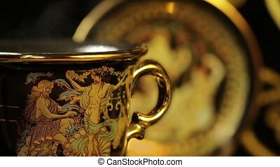 Hot aromatic coffee in a beautiful gold cup - Greek gods on...