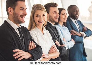 Beautiful business team in formal suits are smiling while...
