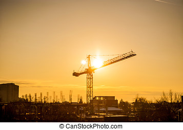 Sunset through a crane in industrialized area of city....