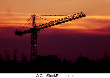 Vibrant sunset with crane silhouette in frame