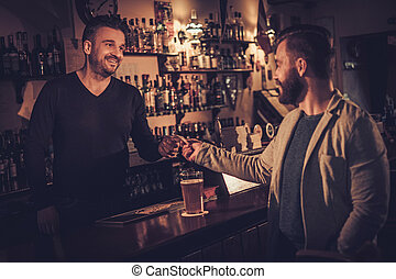 Stylish man paying for beer by card to bartender in pub.