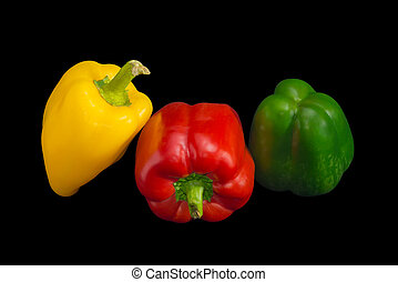 Yellow, red and green bell peppers on a dark background