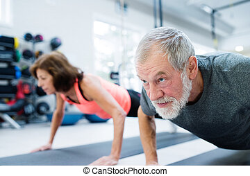Senior couple in gym working out, doing push ups - Beautiful...