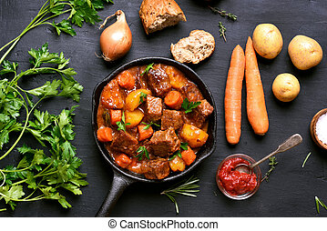 Stewed beef with potatoes and carrots in cast iron pan on...