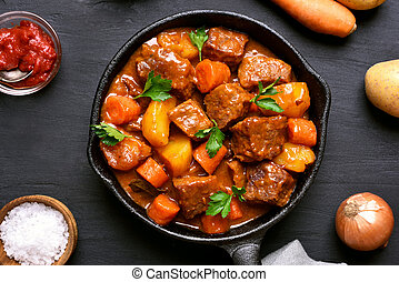 Beef meat stewed with potatoes and carrots in cast iron pan...