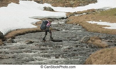 Young girl walks through the mountain river. Norway
