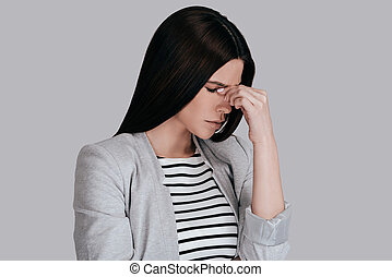 Feeling so tired. Frustrated young woman in smart casual...