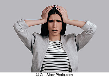 Terrible headache. Frustrated young woman in smart casual...