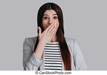 Shocking news! Surprised beautiful young woman in smart...