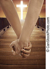Man and woman holding hand together with cross religion symbol