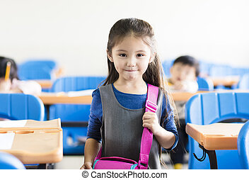 happy little girl student  in the classroom