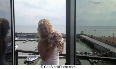 Beautiful young blonde woman on balcony in lingerie -...