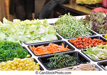 Various vegetables mixed on salad bar.