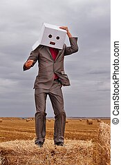 Man standing in park with cardboard box over his head - a...