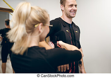 Happy man in ems suit and woman helping him putting it on -...