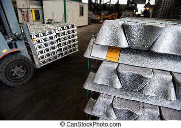 Stack of raw aluminum ingots in aluminum profiles factory,...