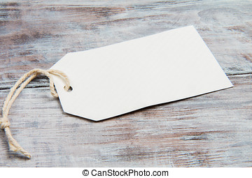White blank tag with string on gray wooden background