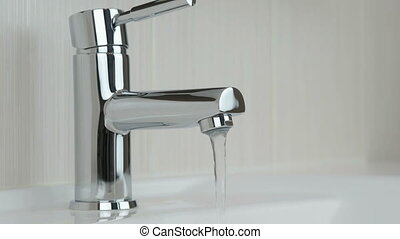 Male hands closing chrome-plated tap of water. Close-up