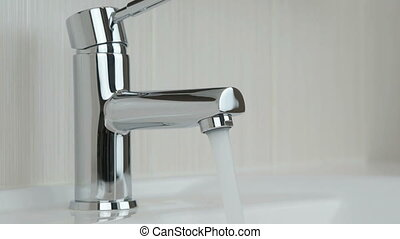 Strong stream of water pouring from the chrome tap - The...
