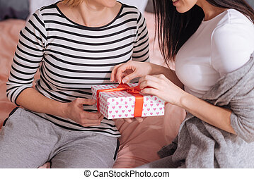 Excited graceful woman opening a present - Do not rush....