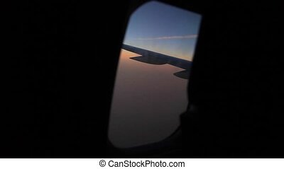 Airplane flying view from cabin clouds at sunset