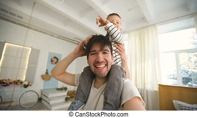 Happy father carrying his smiling son on neck and making selfie on video in bedroom
