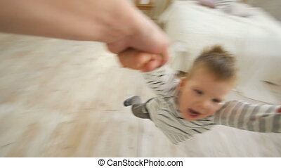 Little boy spinning around and around laughing and smiling at the end of his fathers arms at home
