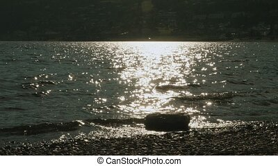 Stone and sun reflection on the lake