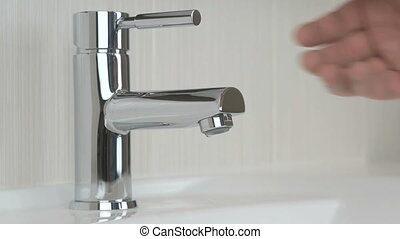 Male hands opening chrome-plated tap for washing hands
