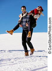 Couple playing in snow. Man giving woman piggyback ride on winter vacation.