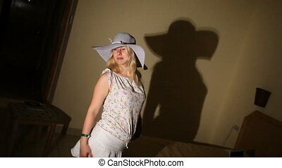 Young woman in hut posing in room - Young blonde woman in...