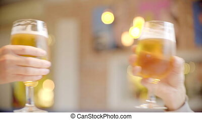 Clinking glasses with beer in bar
