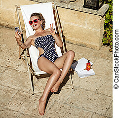 smiling woman in chaise longue taking selfie with cellphone...