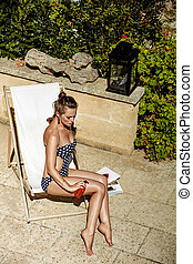 elegant woman in chaise longue applying SPF while sitting -...