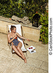 woman in chaise longue applying suntan lotion while sitting...
