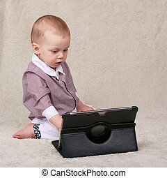 Baby busy using an electronic tablet while sitting on...