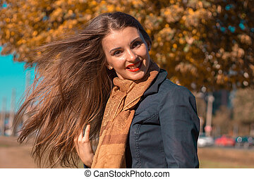 beautiful girl stands in the Park in the Sun and her hair...