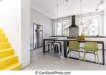 Minimalist kitchen seen from anteroom with yellow staircase