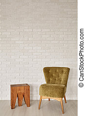 Green armchair and wooden stool at brick wall background