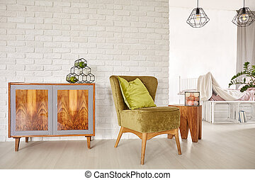 Wooden commode and armchair in living room interior