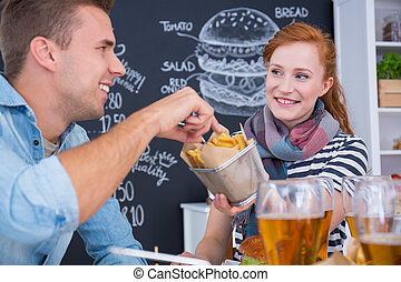 Sharing junk food - Smiled girl is sharing junk food with...
