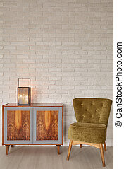 Lantern on wooden commode close to cozy armchair