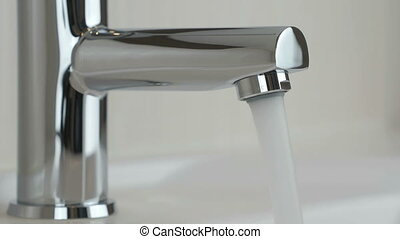 Water under strong pressure flows from a water tap - The...