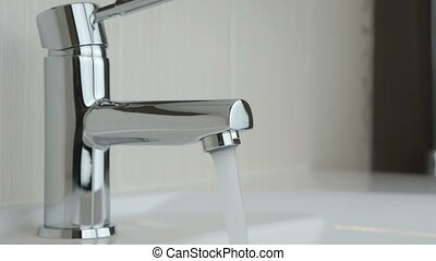 Flow of water pouring from chrome-plated faucet - Stylish...